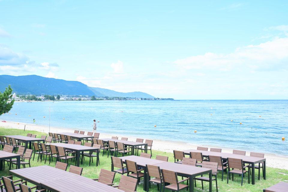 穏やかな琵琶湖の湖面を背景に、大自然に包まれたビーチウェディングの説明画像